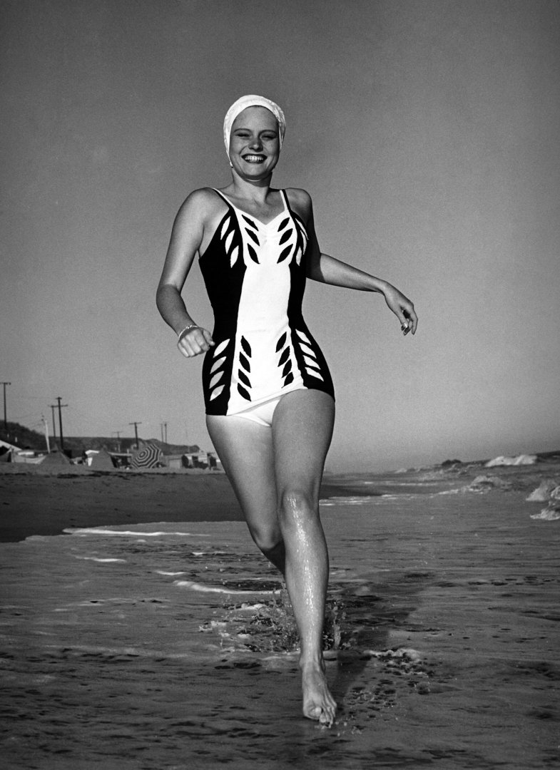Actress Alexis Smith in a swimming costume running along the beach in southern California, USA circa 1940. (Photo by FPG/Getty Images) - thechicflaneuse
