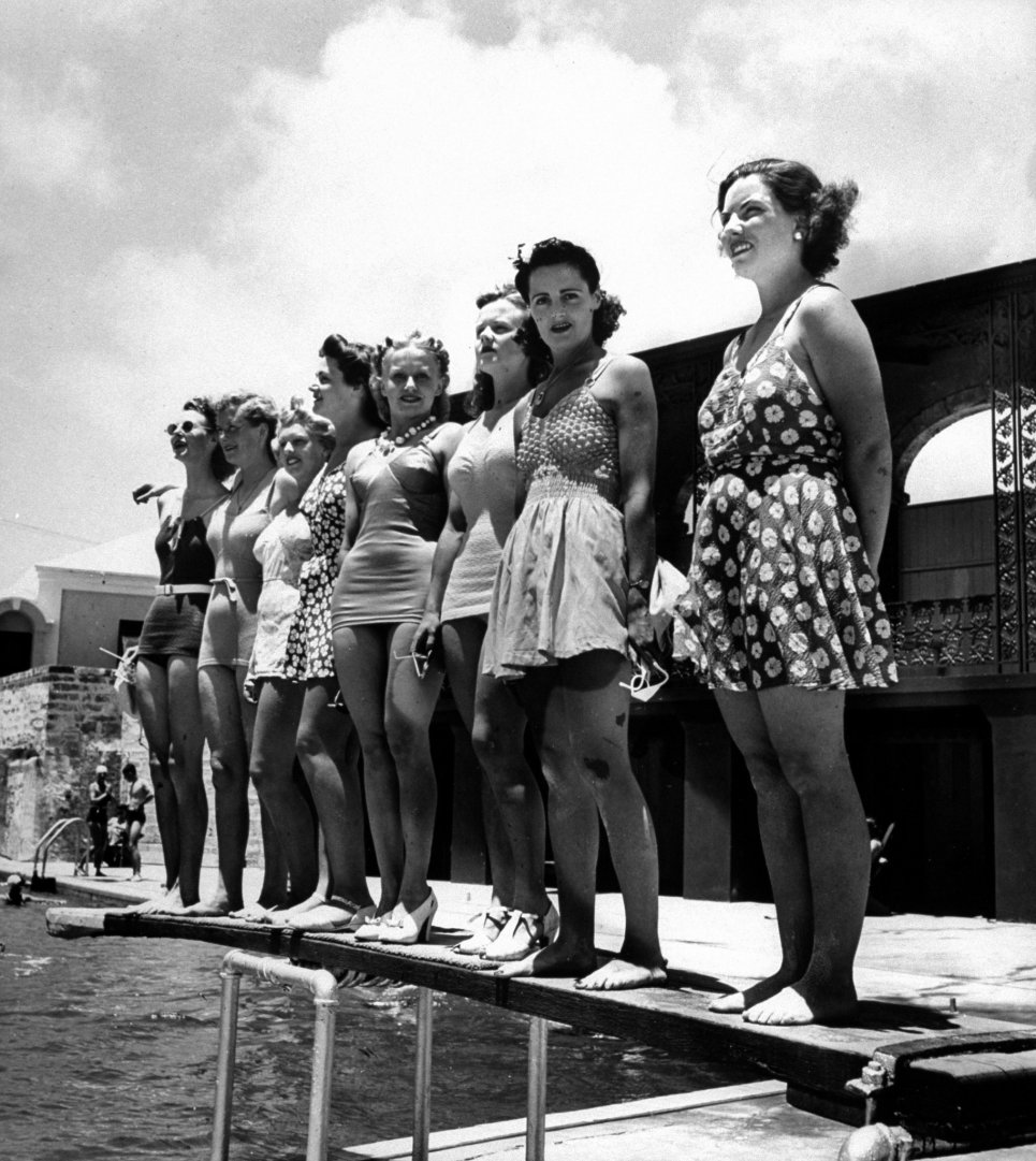 Bathing suit clad female members of the British Imperial Censorship Staff, who call themseleves the censorettes, standing poolside at the Princess Hotel, which also serves as their offices on the island.