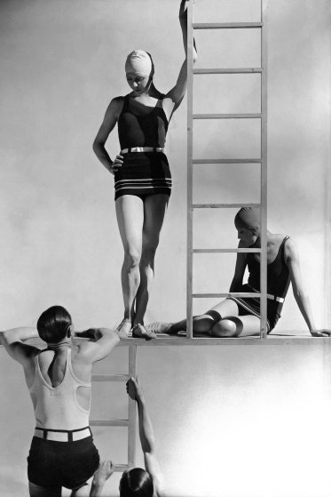 Two men wearing bathing suits (jersey tank tops and belted trunks) climbing up ladder toward two models (the one standing on the left is Georgia Graves) wearing belted one-piece jersey bathing suits (Ondine) with stripes on the bottom; designed by Lucien Lelong; bathing caps. (Photo by George Hoyningen-Huene/Condé Nast via Getty Images)-thechicflaneuse