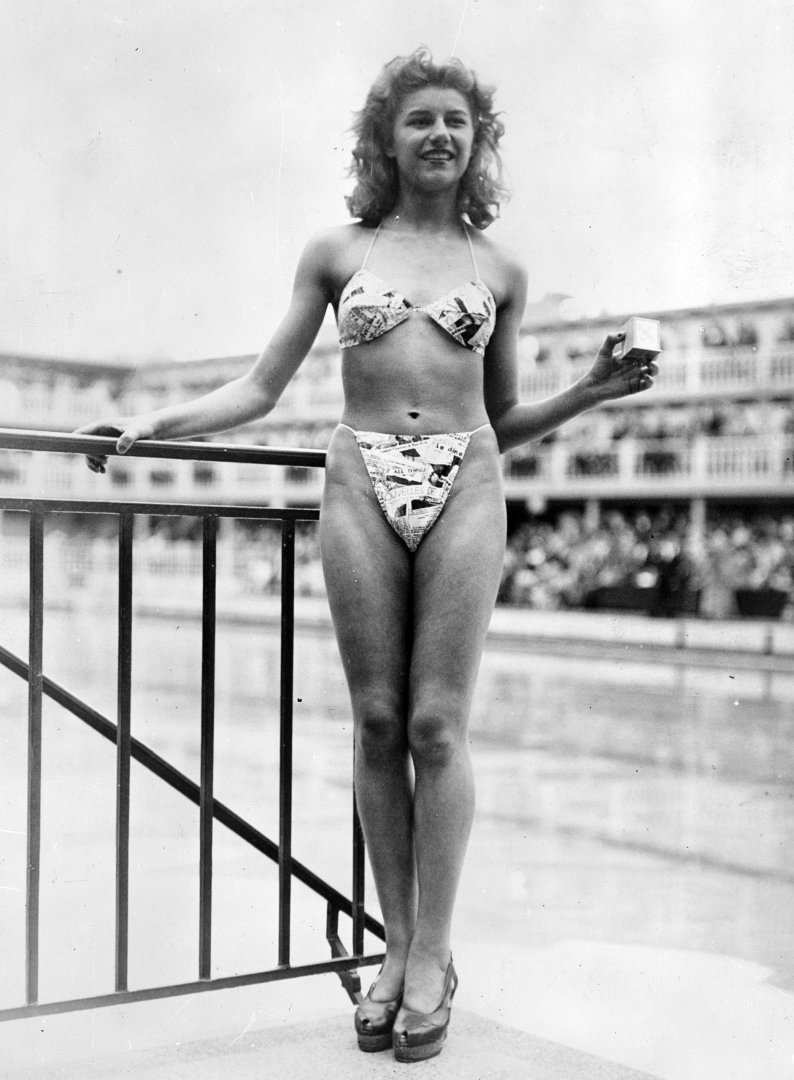 The new 'Bikini' swimming costume (in a newsprint-patterned fabric), which caused a sensation at a beauty contest at the Molitor swimming pool in Paris. Designer Louis Reard was unable to find a 'respectable' model for his costume and the job of displaying it went to 19-year-old Micheline Bernardini, a nude dancer from the Casino de Paris. She is holding a small box into which the entire costume can be packed. Celebrated as the first bikini, Luard's design came a few months after a similar two-piece design was produced by French designer Jacques Heim. (Photo by Keystone/Getty Images) - thechicflaneuse