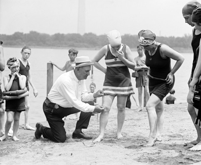 Woman having her swimsuit measured for length violations on a Washington DC beach in the 1920s (silver print), 1922. (Photo by GraphicaArtis/Getty Images) thechicflaneuse