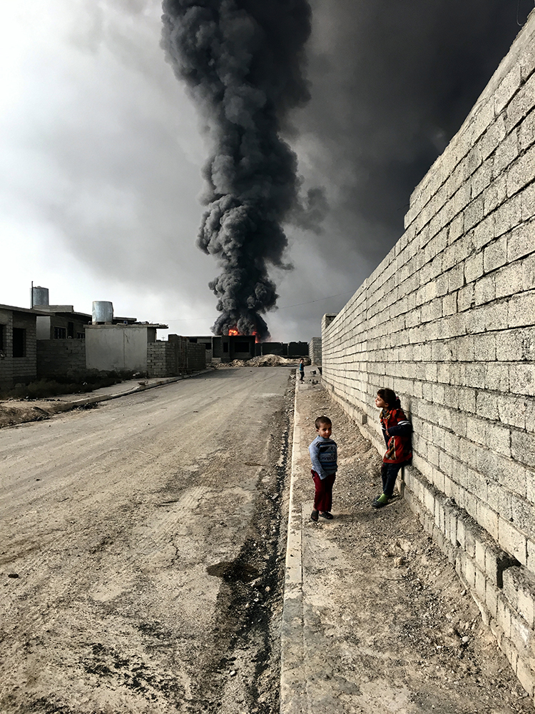 """Sebastiano Tomada Brooklyn, New York Grand Prize Winner, Photographer of the Year iPhone 6s Children of Qayyarah """"Children roam the streets in Qayyarah near the fire and smoke billowing from oil wells, set ablaze by ISIS militants."""""""