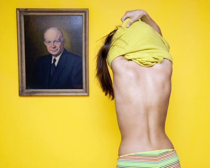 Olivia Locher I-fought-the-law-Ohio disrobe in front of portrait of a man