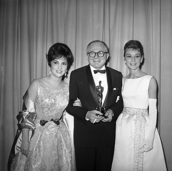 Actress Gina Lollobrigida shown with director Billy Wilder in Santa Monica, California on April 17, 1961, after Wilder was given an Oscar for being named top director of the year for his work in ìThe Apartment.î Miss Lollobrigida made the presentation of the Oscar. At right is actress Audrey Hepburn. (AP Photo)