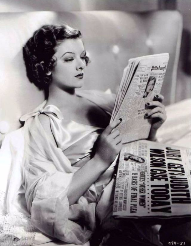Myrna Loy reading a newspaper