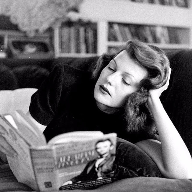 Rita Hayworth reading a book